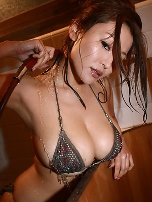 Sizzling asian hottie soaps up her giant plump tits in a bikini
